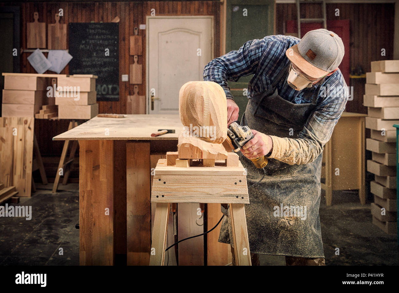 Experienced carpenter in work clothes and small buiness owner working in woodwork workshop, processes the board with an angle grinder on the table is  Stock Photo