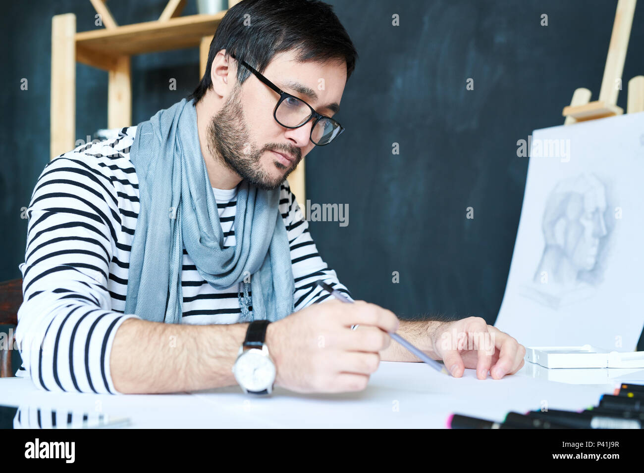 Stylish man painting with pencil - Stock Image