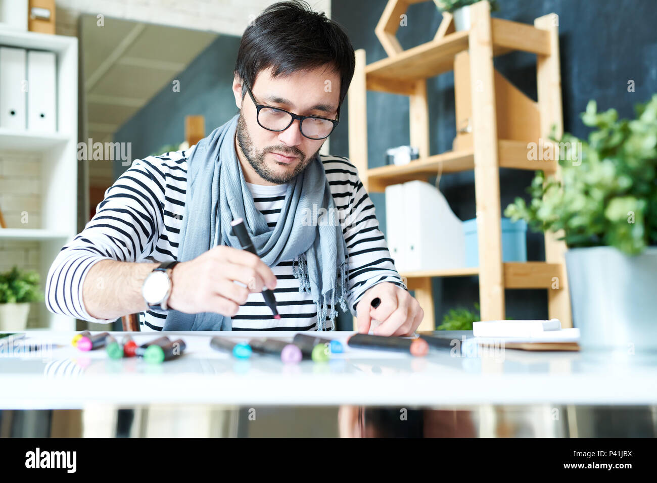 Bearded man working on new painting - Stock Image
