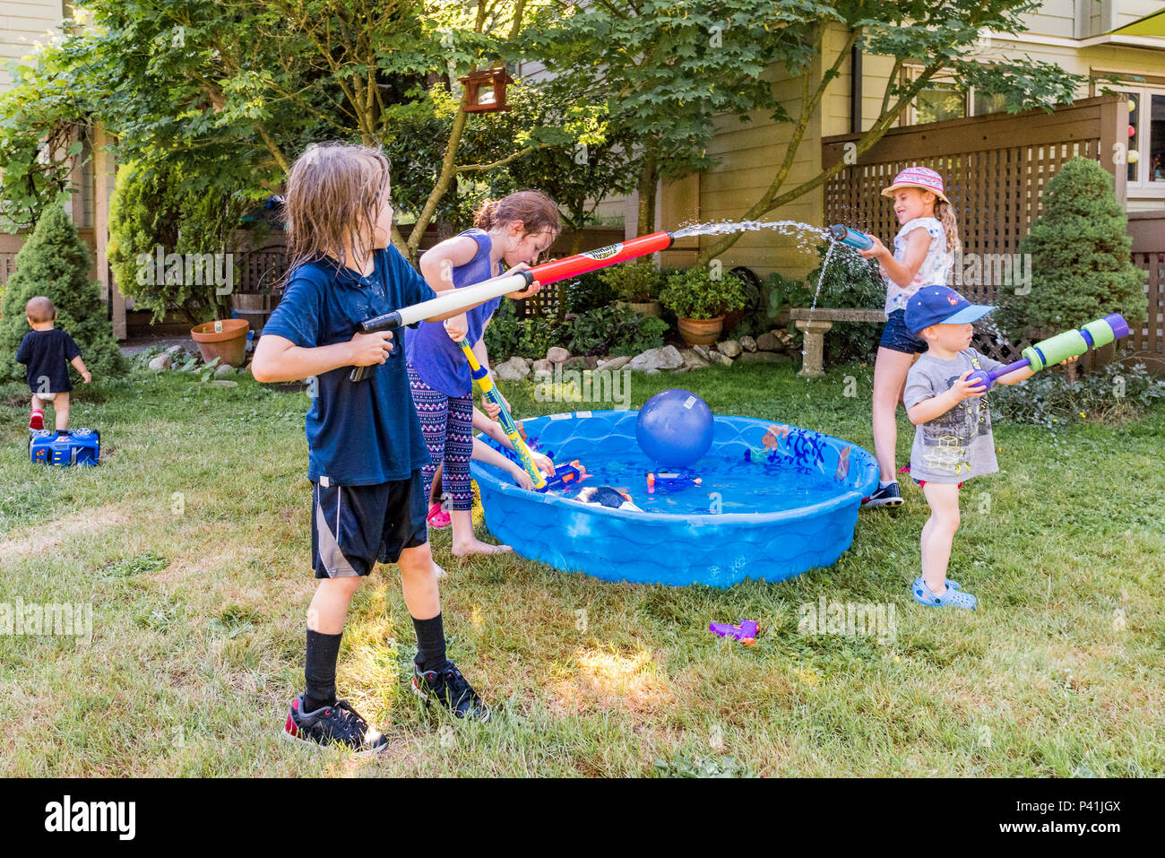 Keeping cool, summer fun,. Kids have friendly backyard water fight. - Stock Image