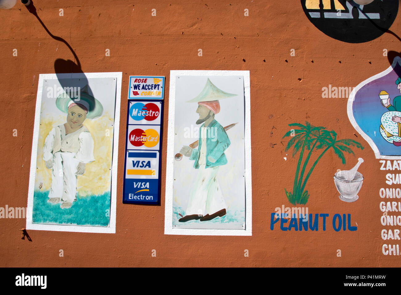 Hand painted advertisement for oil, spices and credit cards on a shop wall in the Bo-Kaap neighborhood in Cape Town, South Africa. - Stock Image