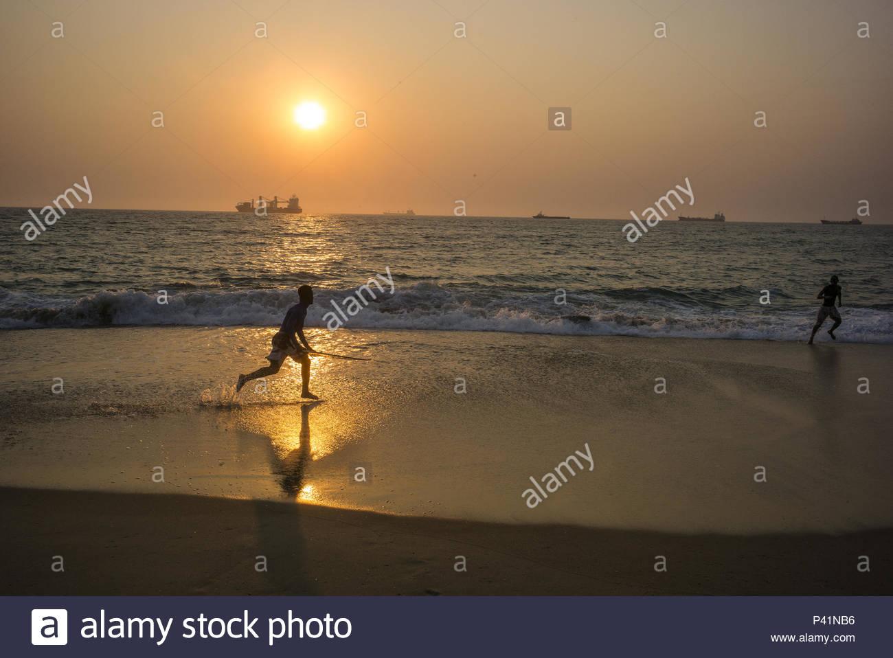 A man runs along the coastline in Angola. - Stock Image