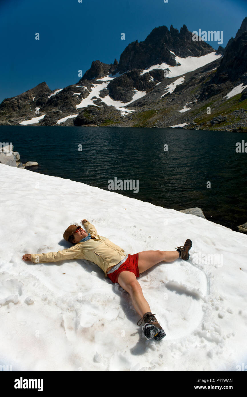 A woman makes snow angles in the August snow around Cecil lake, our highest lake at 10,239 in the Ansel Adams Wilderness of the High Sierra mountains. - Stock Image