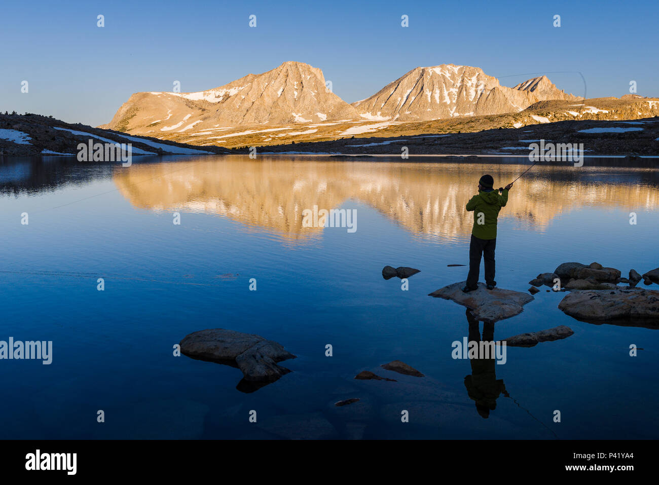 Sunrise fly fishing at French Lake with the reflections of Merriam peak, Royce peak and Feather Peak in the High Sierra mountains near French Canyon. - Stock Image