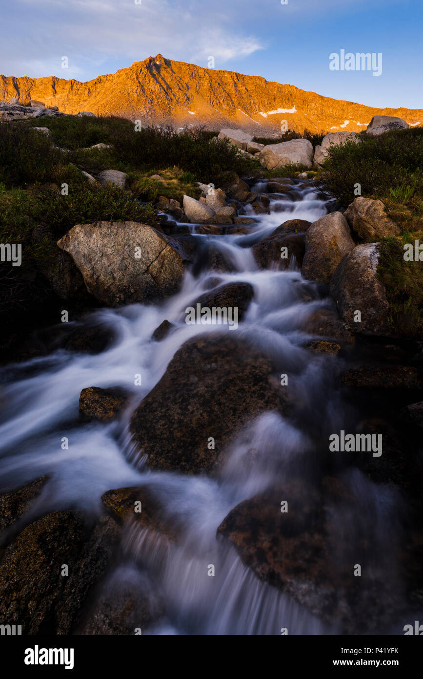 Last light on the back of the Four Gables with mountain stream just below Steelhead Lake in the High Sierra mountains over Pine Creek Pass, California - Stock Image