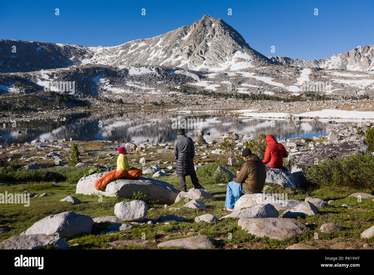 Backpackers drink coffee at sunrise at L Lake in the High Sierra mountains over Pine Creek Pass west of Bishop, California, July 2016. - Stock Image