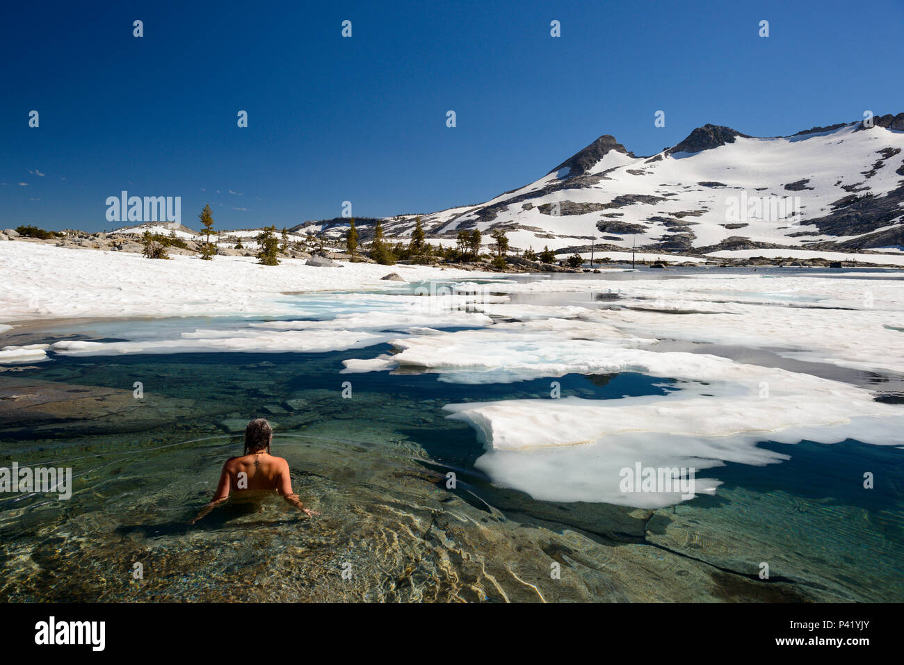 A woman swims in the ice covered waters of Lake Aloha in the Desolation wilderness area in south lake tahoe. Stock Photo
