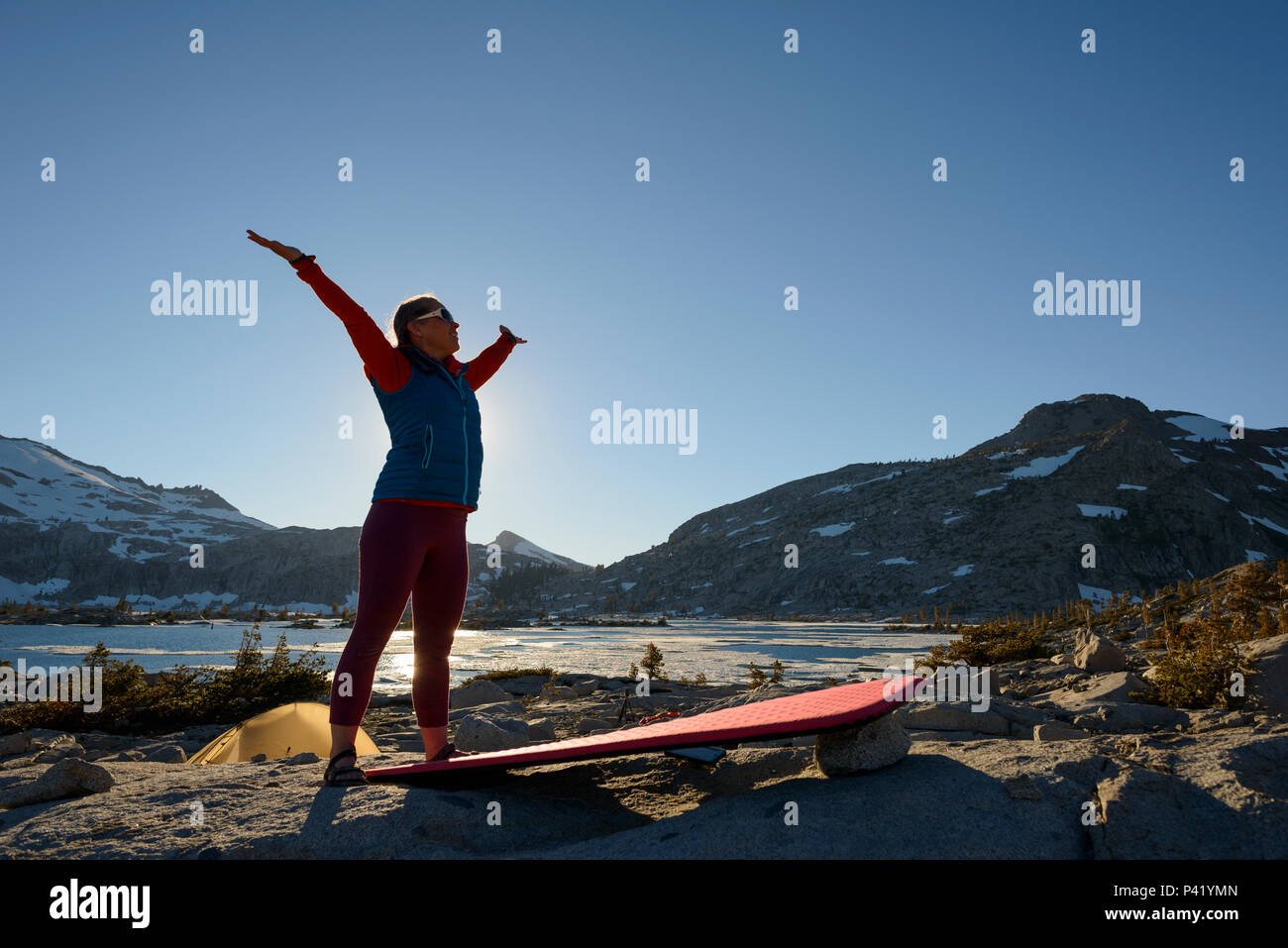 A woman backpacker does yoga at camp in the granite around Lake Aloha in the Desolation wilderness hike in south lake tahoe, California, USA. Stock Photo