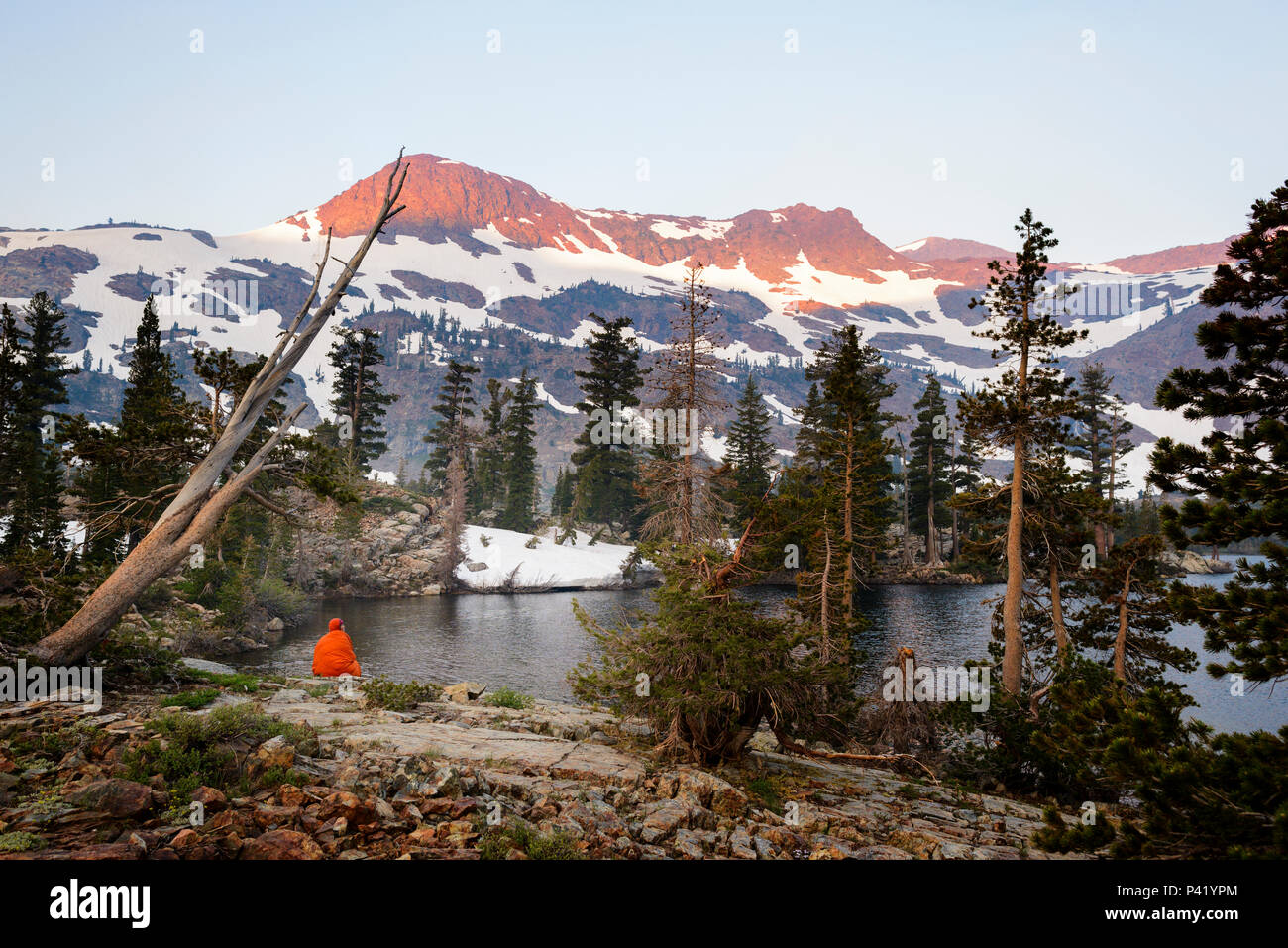 Backpacker watching the smoky sunrise at Half Moon Lake in the Desolation wilderness hike in south lake tahoe, California,USA. - Stock Image