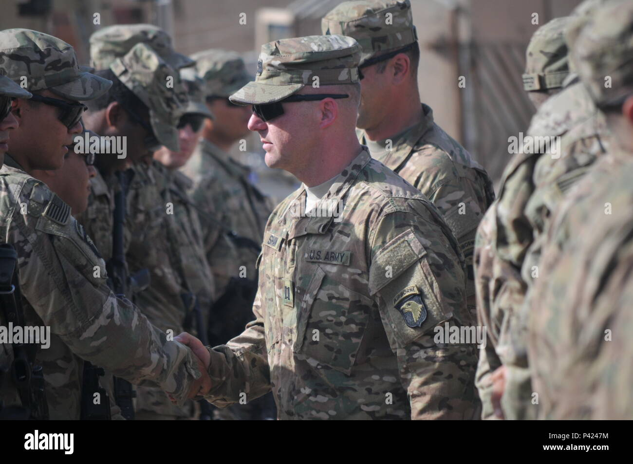 Cpt. Justin Shaw, center, commander of Company D, 1st Battalion, 26th Infantry Regiment, Task Force Strike, shakes the hands of Soldiers of Company D after their patching ceremony June 3, 2016, in Taji, Iraq. Soldiers are allowed to wear the patch for the rest of their careers, signifying service in a theater of combat operations with the 101st Airborne Division (Air Assault). Taji is one of four Combined Joint Task Force - Operation Inherent Resolve building partner capacity locations dedicated to training Iraqi Security Forces. (U.S. Army photo by 1st Lt. Daniel Johnson/Released) - Stock Image