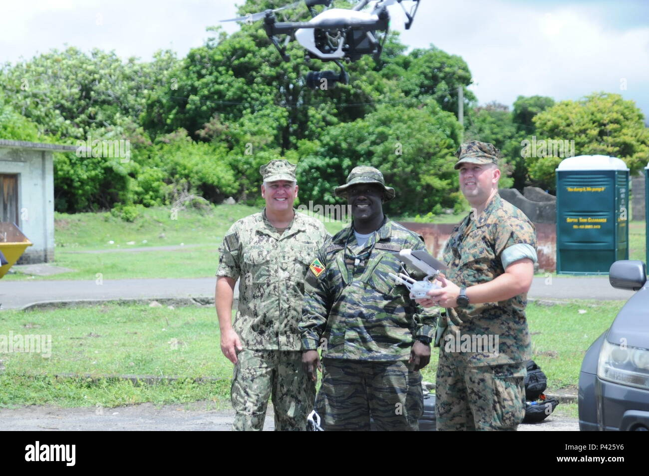 1st Lt. Regiwell Franics (middle), of the Saint Kitts and Nevis Defense Force, shows off his drone to Rear Adm. Scott Jerabek (far left) and Maj. Bryant Pater at Pearls Airport in Grenada, June 7, 2016. Francis is using his drone to provide aerial footage of exercises during Tradewinds Phase I Field Exercise held from June 05-14 in Grenada. Tradewinds 2016 is a joint combined exercise conducted in conjunction with partner nations to enhance the collective abilities of defense forces and constabularies to counter transnational organized crime and to conduct humanitarian/disaster relief operatio - Stock Image