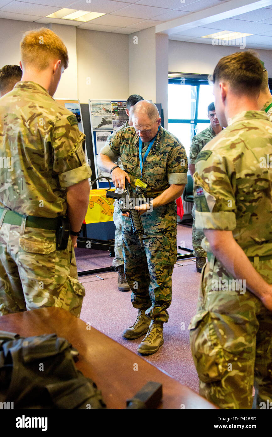 Commandant of the Marine Corps, Gen. Robert B. Neller, inspects a Royal Marines' weapon at Her Majesty's Naval Base, Clyde, Scotland, June 2, 2016. Neller visited the 43 Commando Fleet Protection Group Royal Marines to view their equipment and understand their capabilities. (U.S. Marine Corps photo by Staff Sgt. Gabriela Garcia/Released) - Stock Image