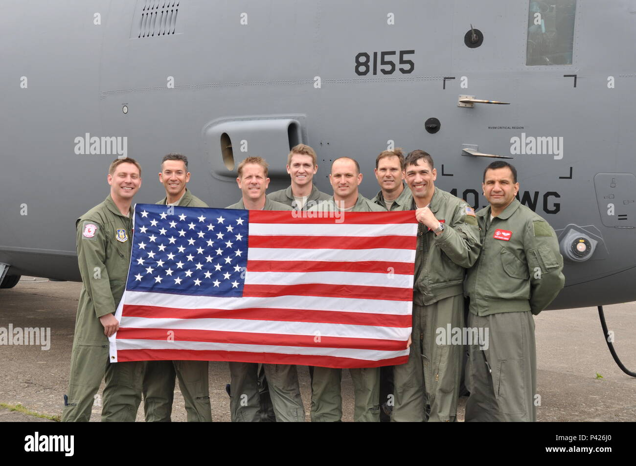 Members of the 815th Airlift Squadron pose with a U.S. flag next to the C-130J.  The 815th AS provided aerial transport of U.S. and French Airborne troops for the scheduled massive parachute drops.  More than 380 service from Europe and affiliated D-Day historical units are participating in the 72nd anniversary as a part of Joint Task Force D-Day 72.  The Task Force, based in Sainte-Mère-Église, France, is supporting local events across Normandy, from May 30 - 6 June, 2016 to commemorate the selfless actions by all of the allies on D-Day that continue to resonate 72 years later.  (U.S. Air For Stock Photo