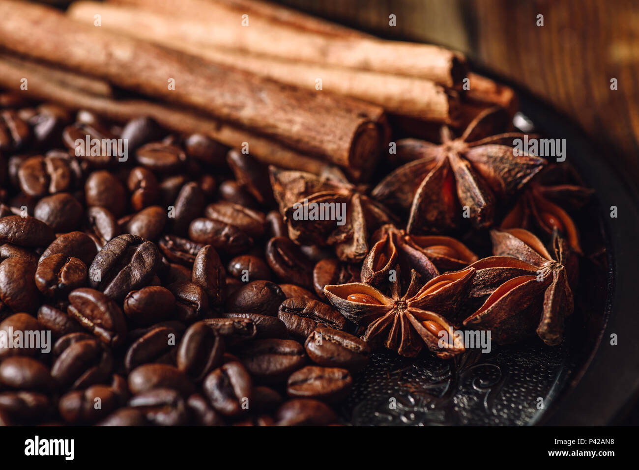 Coffee Beans with Cinnamon Sticks and Chinese Star Anise on Metal Plate. - Stock Image