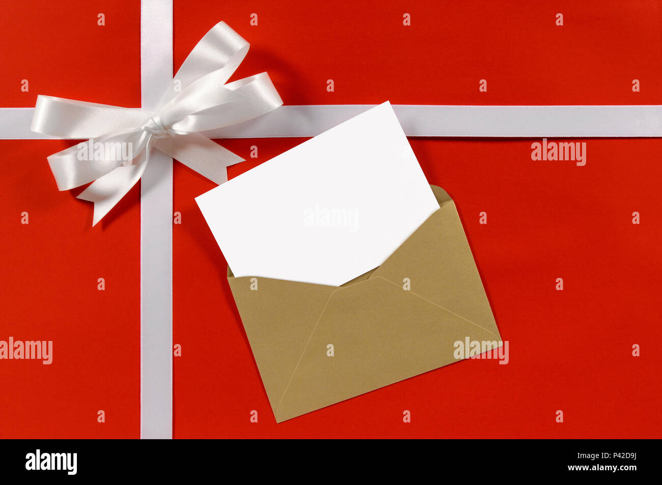 Christmas Or Birthday Card With Gift Ribbon And Bow In White Satin On Red Paper Background Brown Envelope Blank Message