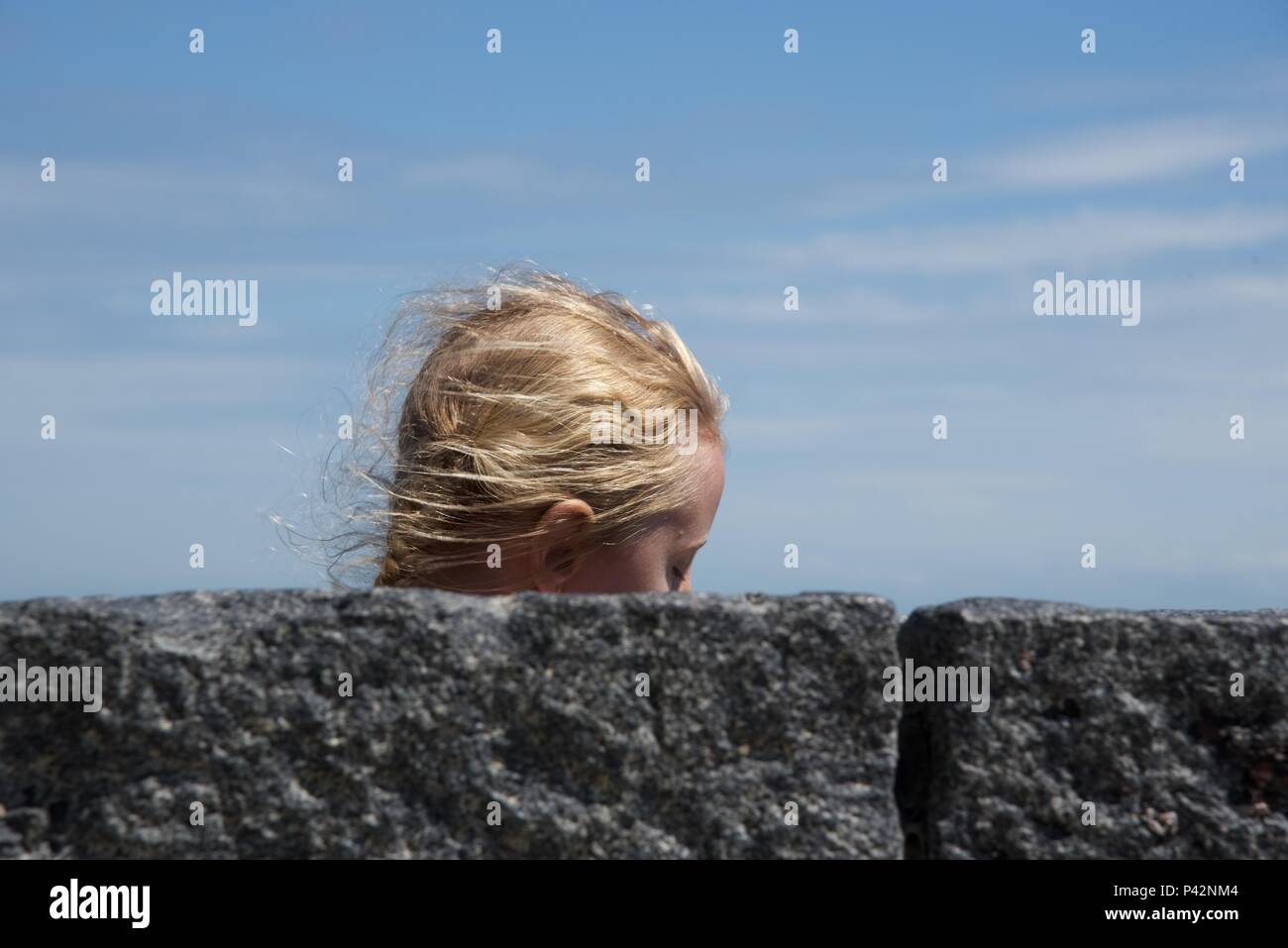 Girl: a fair-haired girl passing behind a sea wall - Stock Image