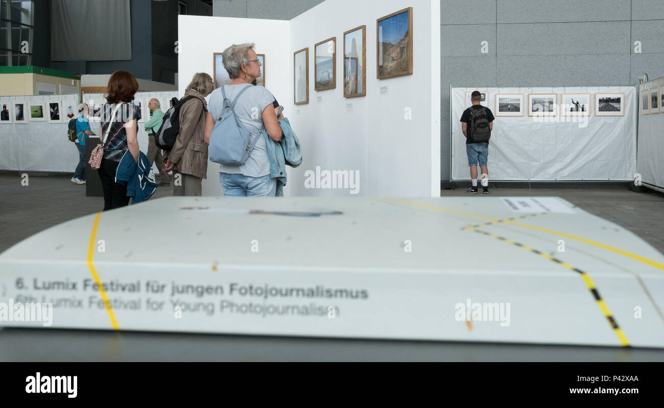 Hanover, Germany. 20th June, 2018. Visitors look at photographs on the subject of flight, which are exhibited in connection with the Lumix Festival. A few months ago, the same pavillon was used to house refugees. Credit: Jochen Lübke/dpa/Alamy Live News - Stock Image
