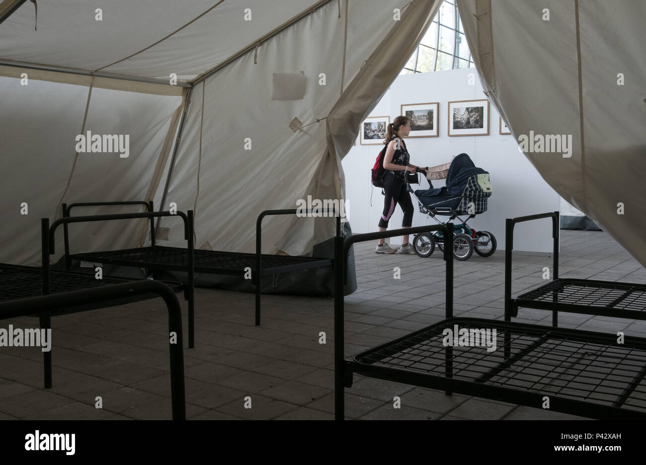 Hanover, Germany. 20th June, 2018. A visitor looks at photographs on the subject of flight, which are exhibited in connection with the Lumix Festival. A few months ago, the same pavillon was used to house refugees. Credit: Jochen Lübke/dpa/Alamy Live News - Stock Image