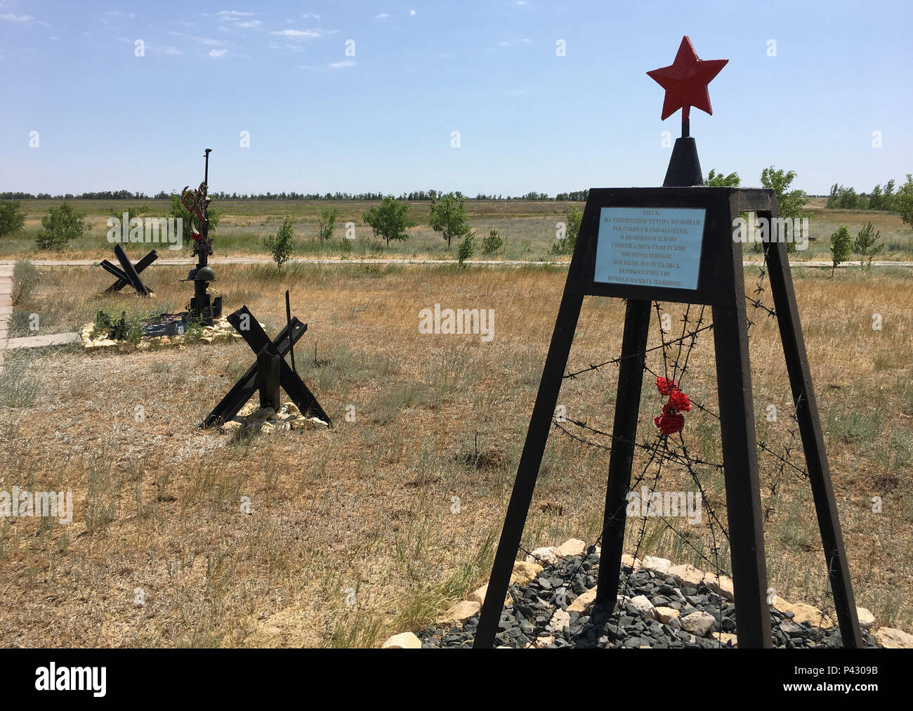 Rossoschka, Russia. 16th June, 2018. A red star stands on a steel framework wrapped in barbed wire behind the anti-tank barriers on the «Rossoschka Military Cemetery». Here not only soldiers of the German Wehrmacht are buried, but also members of the Red Army. Only a narrow street separates today's opponents. The remote memorial commemorates one of the worst chapters in World War II: the Battle of Stalingrad. Credit: Martin Moravec/dpa/Alamy Live News - Stock Image