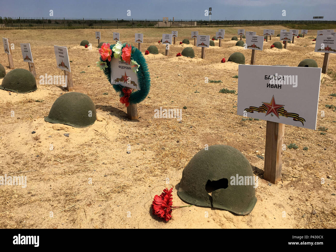 Rossoschka, Russia. 16th June, 2018. Steel helmets and nameplates attached to wooden posts stand at the graves of fallen Red Army soldiers at the «Rossoschka Military Cemetery». Here not only soldiers of the German Wehrmacht are buried, but also members of the Red Army. Only a narrow street separates today's opponents. The remote memorial commemorates one of the worst chapters in World War II: the Battle of Stalingrad. Credit: Martin Moravec/dpa/Alamy Live News - Stock Image