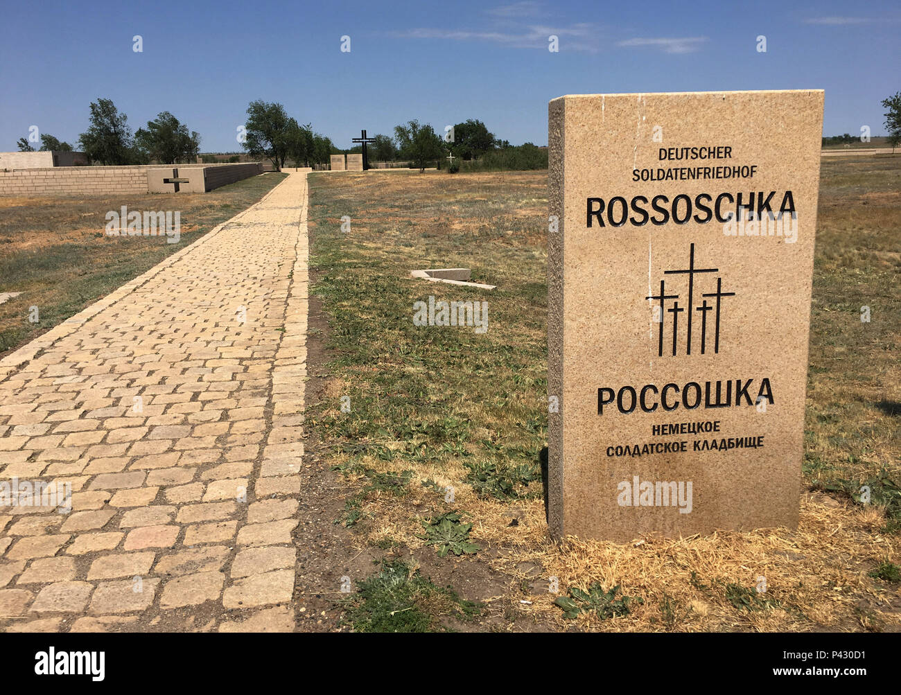 Rossoschka, Russia. 16th June, 2018. The inscription «Military Cemetery Rossoschka» is written on a gravestone at the entrance in Russian and German. Here not only soldiers of the German Wehrmacht are buried, but also members of the Red Army. Only a narrow street separates today's opponents. The remote memorial commemorates one of the worst chapters in World War II: the Battle of Stalingrad. Credit: Martin Moravec/dpa/Alamy Live News - Stock Image
