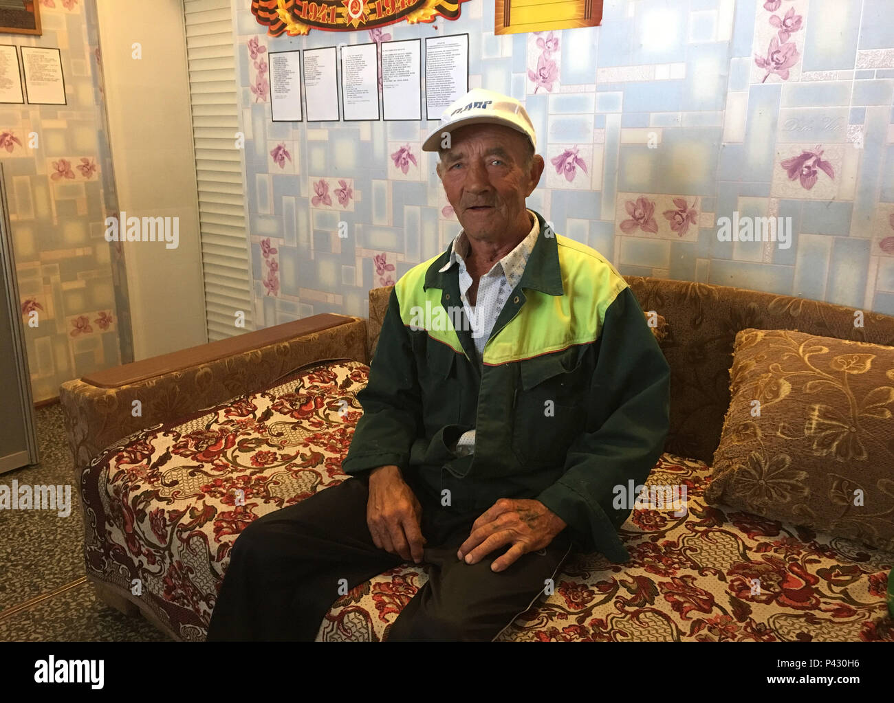 Rossoschka, Russia. 16th June, 2018. Vitaly Danilkin sits on a sofa in the anteroom of a small private museum on the «Rossoschka Military Cemetery». Here not only soldiers of the German Wehrmacht are buried, but also members of the Red Army. The 72-year-old has been working here for three years: mowing the lawn in summer, shoveling snow in winter, keeping the facility in order, everything a janitor would do. Credit: Martin Moravec/dpa/Alamy Live News - Stock Image