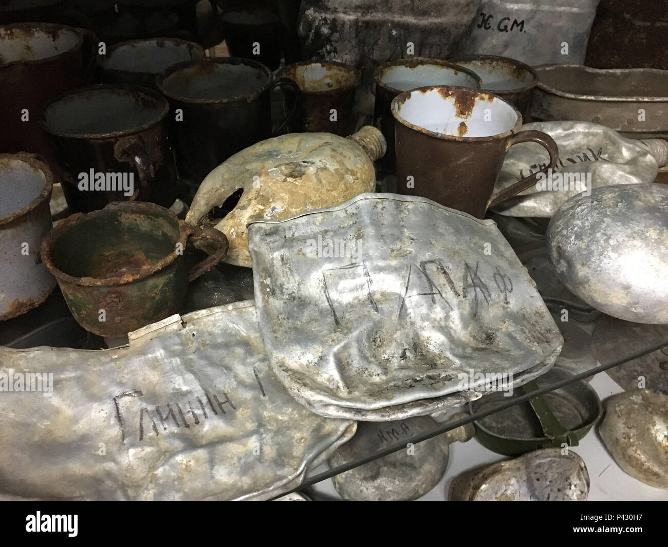 Rossoschka, Russia. 16th June, 2018. Remnants of the Battle of Stalingrad - cups, cookware and other utensils - can be seen in a hut on the «Rossoschka Military Cemetery», where there is a small private museum. Here not only soldiers of the German Wehrmacht are buried, but also members of the Red Army. The 72-year-old has been working here for three years: mowing the lawn in summer, shoveling snow in winter, keeping the facility in order, everything a janitor would do. Credit: Martin Moravec/dpa/Alamy Live News - Stock Image