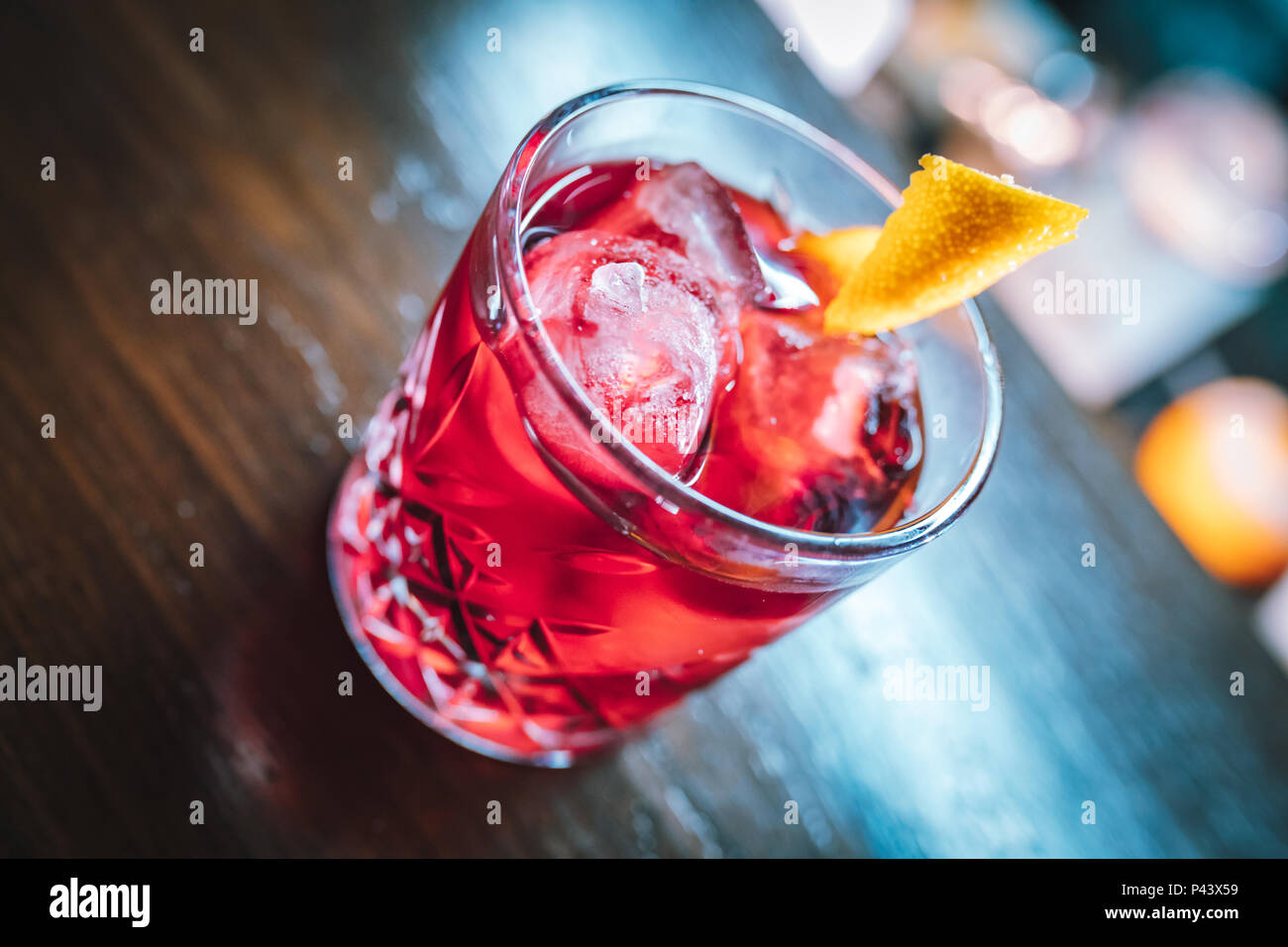 Pink and red Fresh colorful exotic alcoholic cocktail with lemon and ice in the bar. Colorful pink Soft drink with ice on the bar desk. Red cocktail - Stock Image