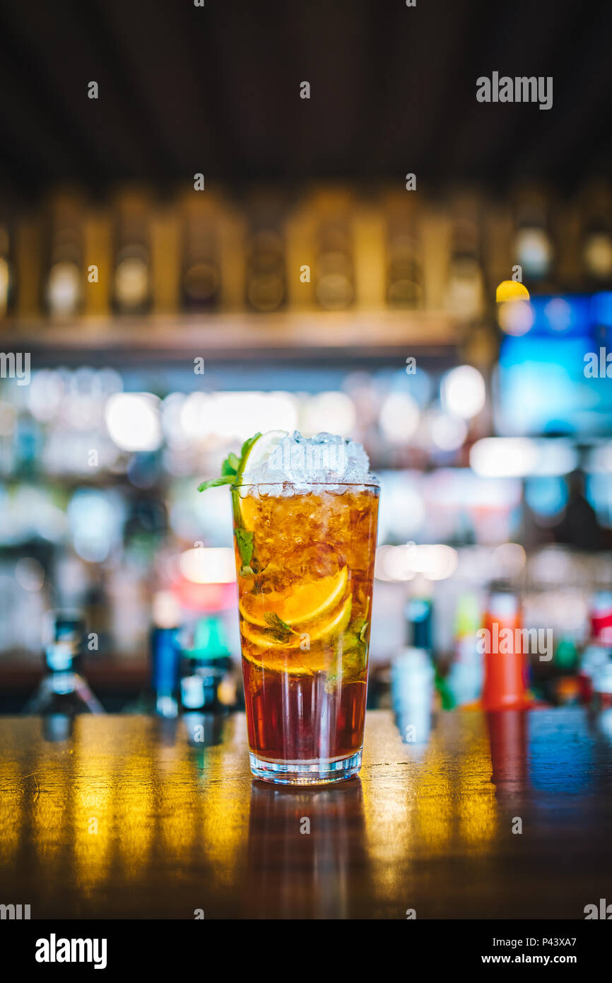 Fresh colorful exotic alcoholic cocktail with lime in the bar. Colorful gold Soft drink with lemons on the bar desk. Jagermeister Mojito Cocktail - Stock Image