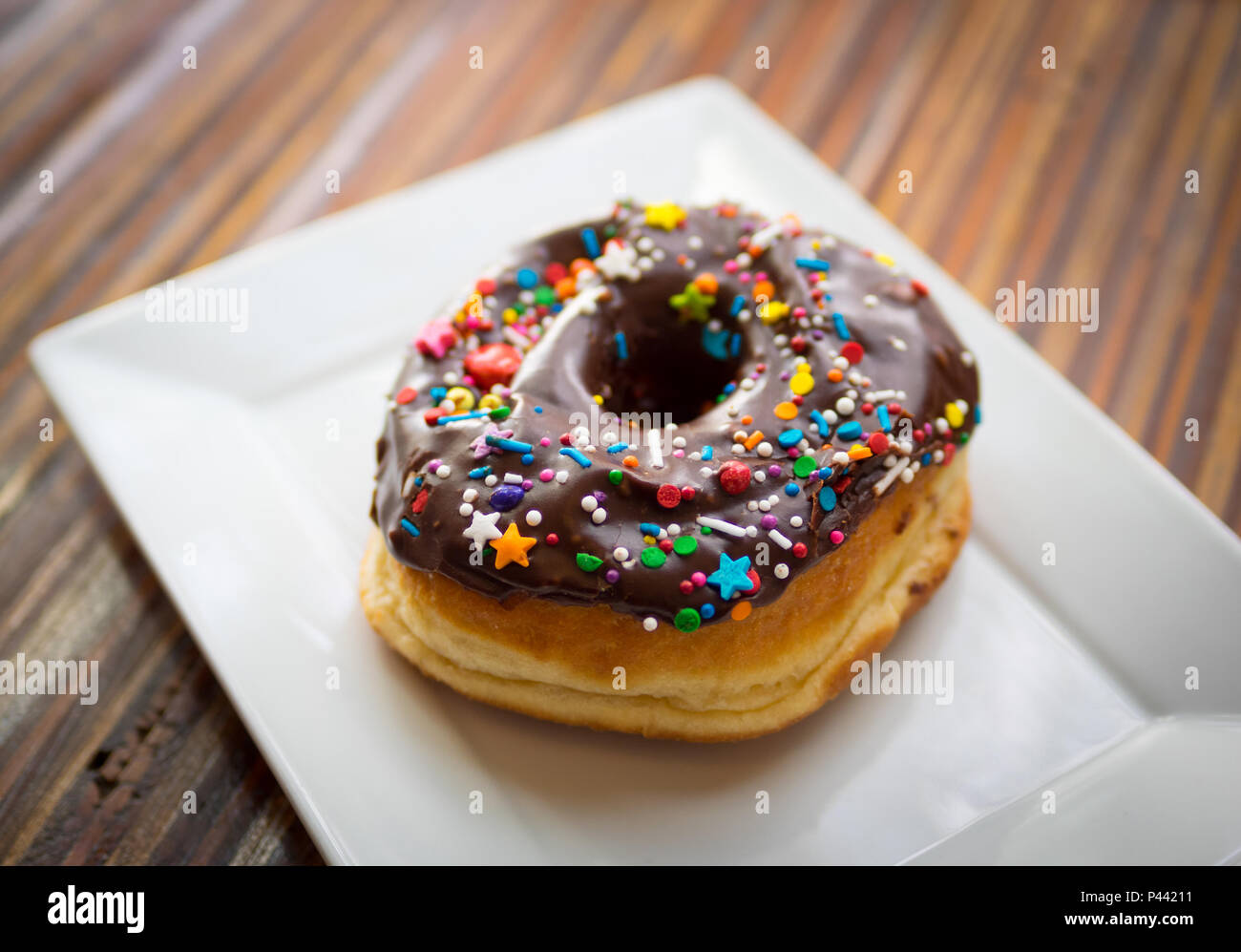 A chocolate donut with sprinkles from Picnic Too, a popular cafe and restaurant in Victoria, British Columbia, Canada. - Stock Image
