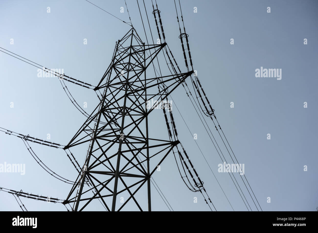 Power Tower industry pole for electricity, close up with cloudy dark sky, low angle view - Stock Image