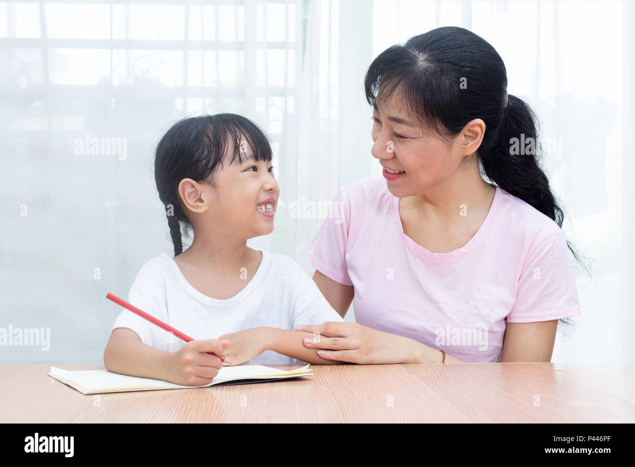 Asian Chinese mother teaching daughter doing homework at home - Stock Image