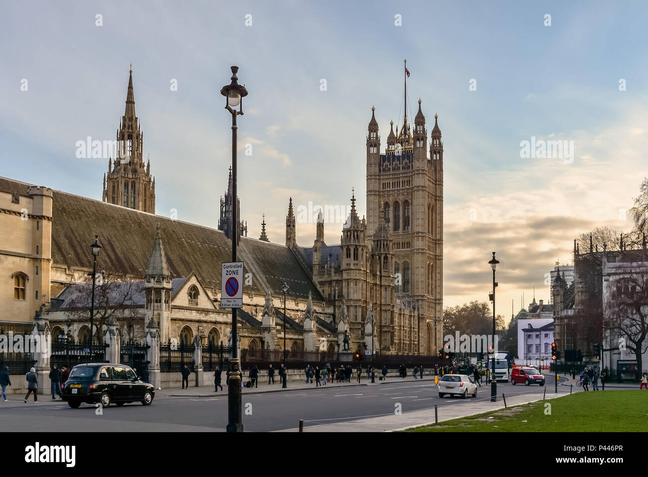 London, UK - January 20, 2015: Central and Victoria Towers of The Palace of Westminster with the bronze statue of Oliver Cromwell and classic British  - Stock Image