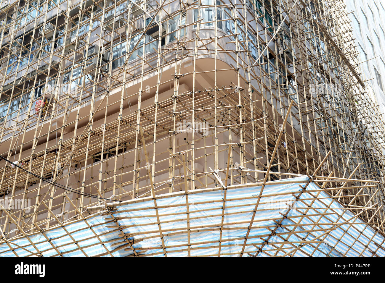 In Hong Kong and China and other parts of Asia, bamboo is often used for scaffolding for real estate construction in place of steel or iron scaffolds - Stock Image