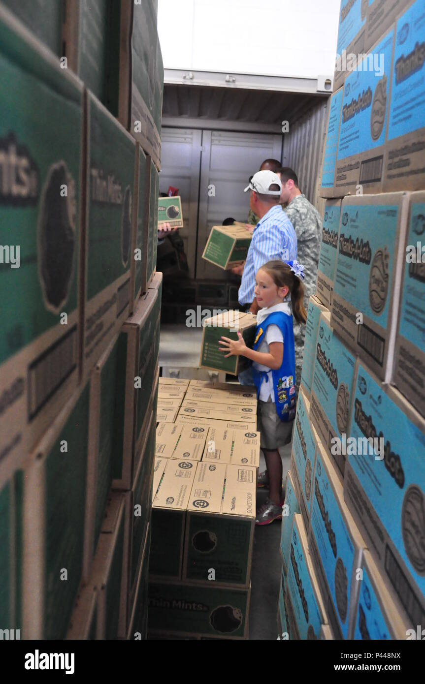 A Girl Scout helps load some of the 24000 boxes of cookies raised