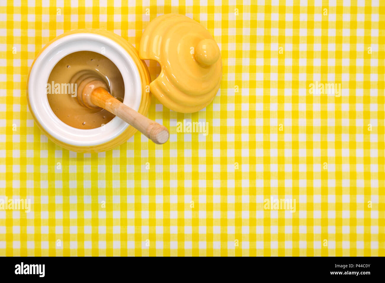 A beehive themed pot full of Manuka honey with wooden dipper on a yellow gingham background with copy space. - Stock Image
