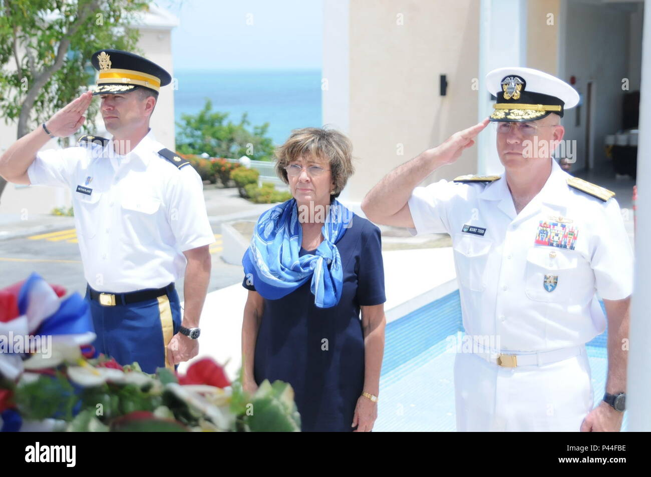 Adm. Kurt W. Tidd (far right), commander of U.S. Southern Command, Linda S. Taglialatela, Chief of the U.S. Mission to Barbados, the Eastern Caribbean and the OECS, and Maj. Louis Netherland, the operations officer at United States liaison office in Barbados and Eastern Caribbean, salute a monument on the campus of St. George's University in Grenada, June 14, 2016. The monument memorializes the U.S. servicemen killed during Operation Urgent Fury in 1983. The event took place after the closing ceremony of Tradewinds 2016. U.S. Army photo by Sgt. Jason Drager. - Stock Image