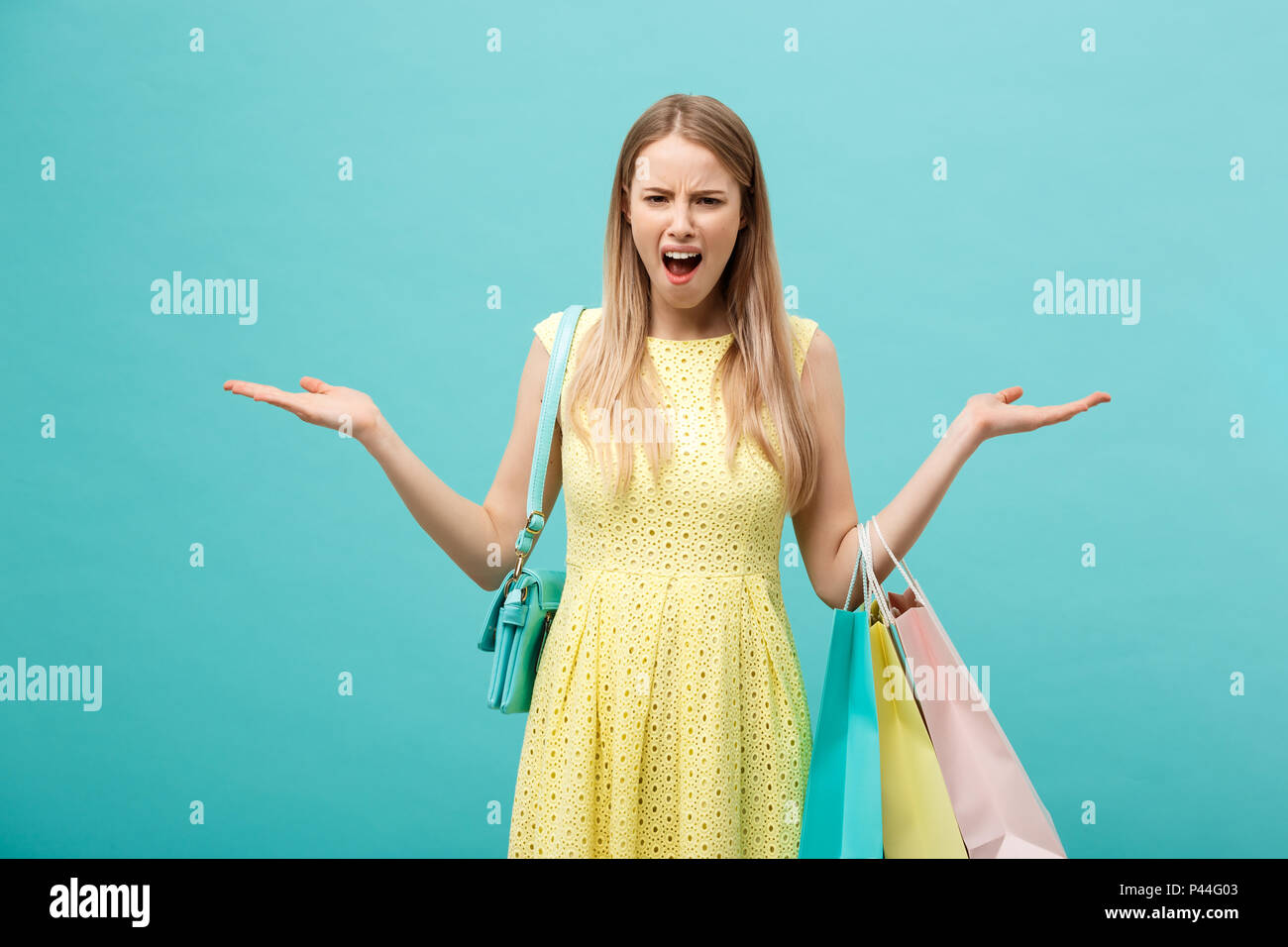 Shoping and Sale Concept: beautiful unhappy young woman in yellow elegant dress with shopping bag. - Stock Image