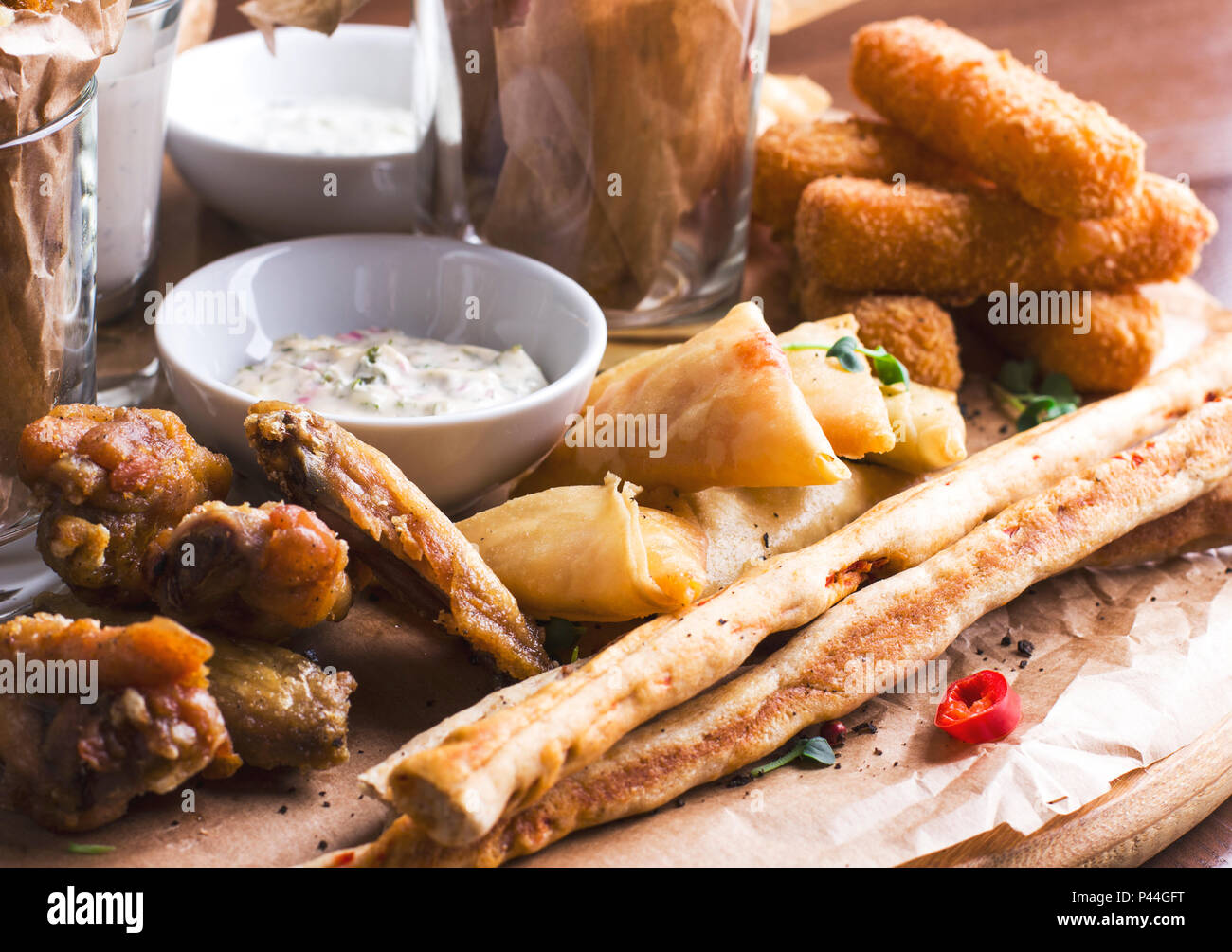 Spicy baked chicken wings, bread sticks with appetizers and sauces on round wooden Board Stock Photo