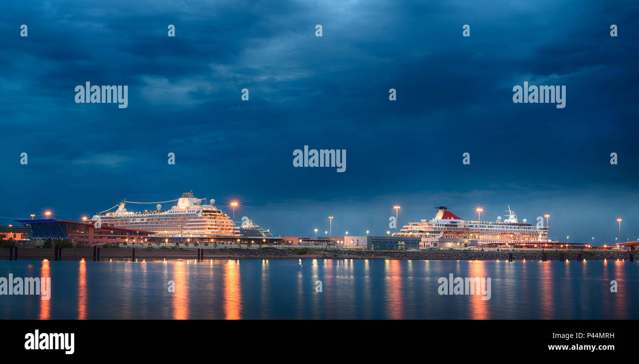 Luxury cruise liners at sea port night view. Two large passengers ships at harbor of Saint Petersburg, Russia - Stock Image