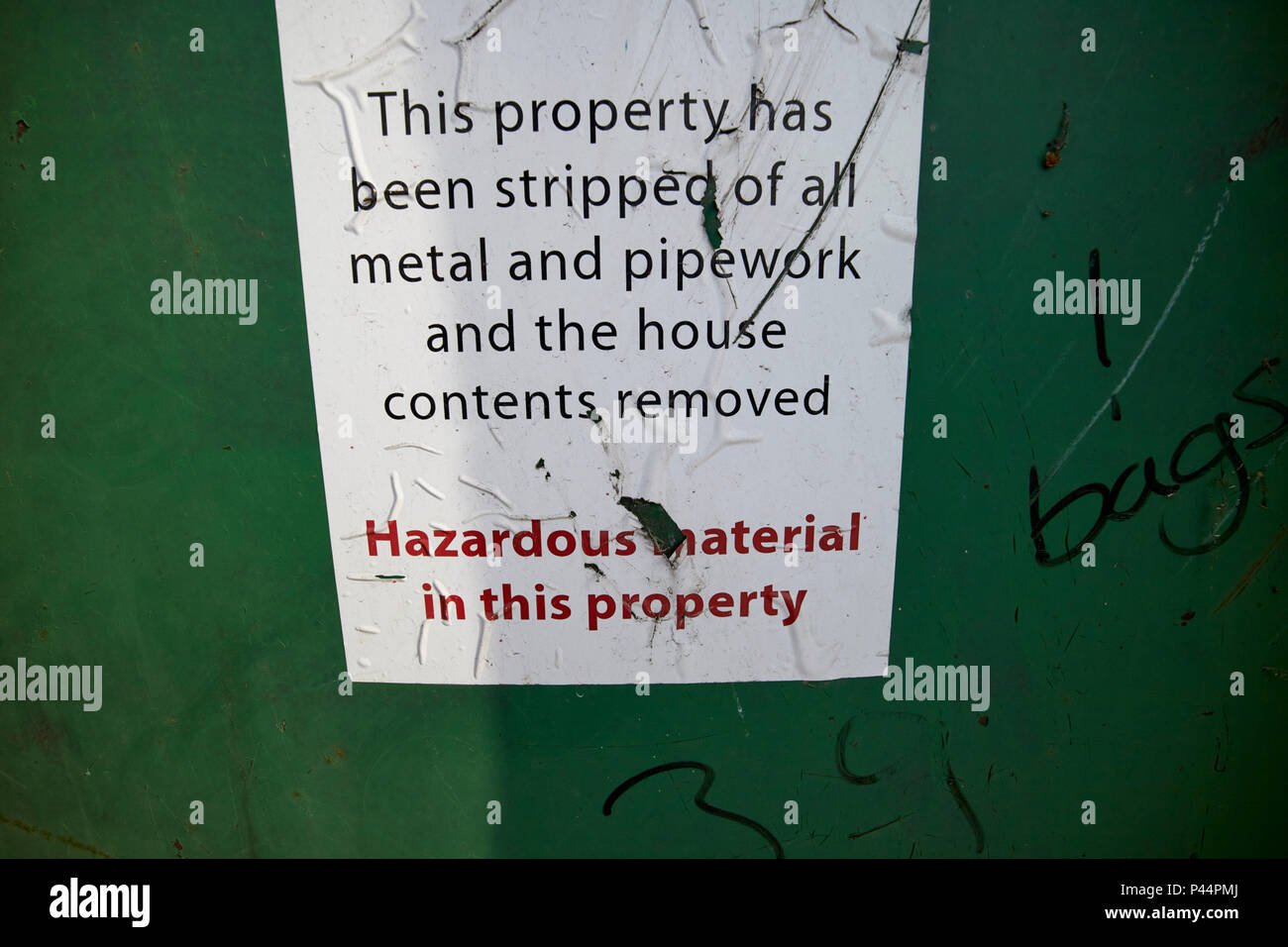 Notice on derelict house saying all contents metal and pipework have been removed and hazardous material Carlisle Cumbria England UK - Stock Image