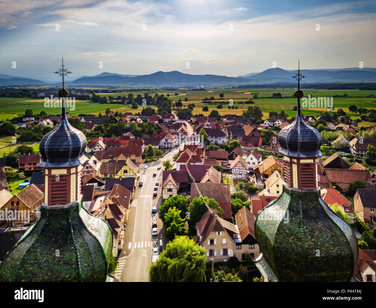 Soaring majestic church Saint Maurice in little french village Ebersmunster. Aerial drone view. Alsace. France. Stock Photo