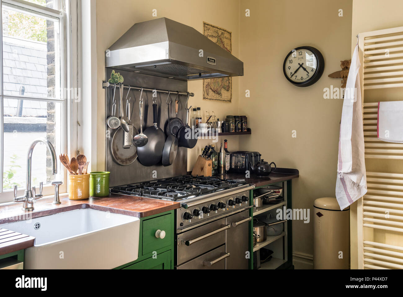 Stainless steel extractor and clock with gas oven at window. - Stock Image