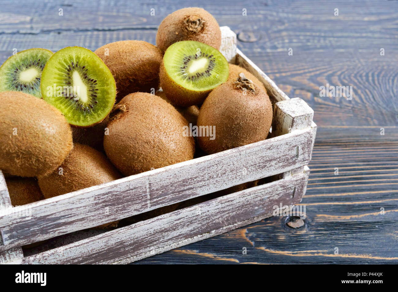 Fresh ripe kiwi fruit in a wooden box on the table. Tropical Fruit. Healthy food. - Stock Image