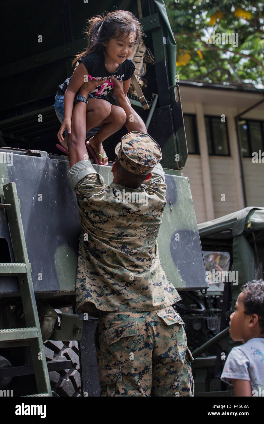 """KANEOHE, Hawaii – Cpl. Romeo Barut, a motor transport operator with Alpha Battery, 1st Battalion, 12th Marine Regiment from Marine Corps Base Hawaii, helps a child down from the back of a Medium Tactical Vehicle Replacement during a """"Meet the Community Heroes"""" event at the Kaneohe Public Library in Kaneohe, Hawaii, June 23, 2016. The Marines were given the opportunity to interact with children and parents from the community. Children got the chance to meet police officers, firefighters and Marines. Multiple vehicles from the organizations were on display for all the children to see and play in - Stock Image"""