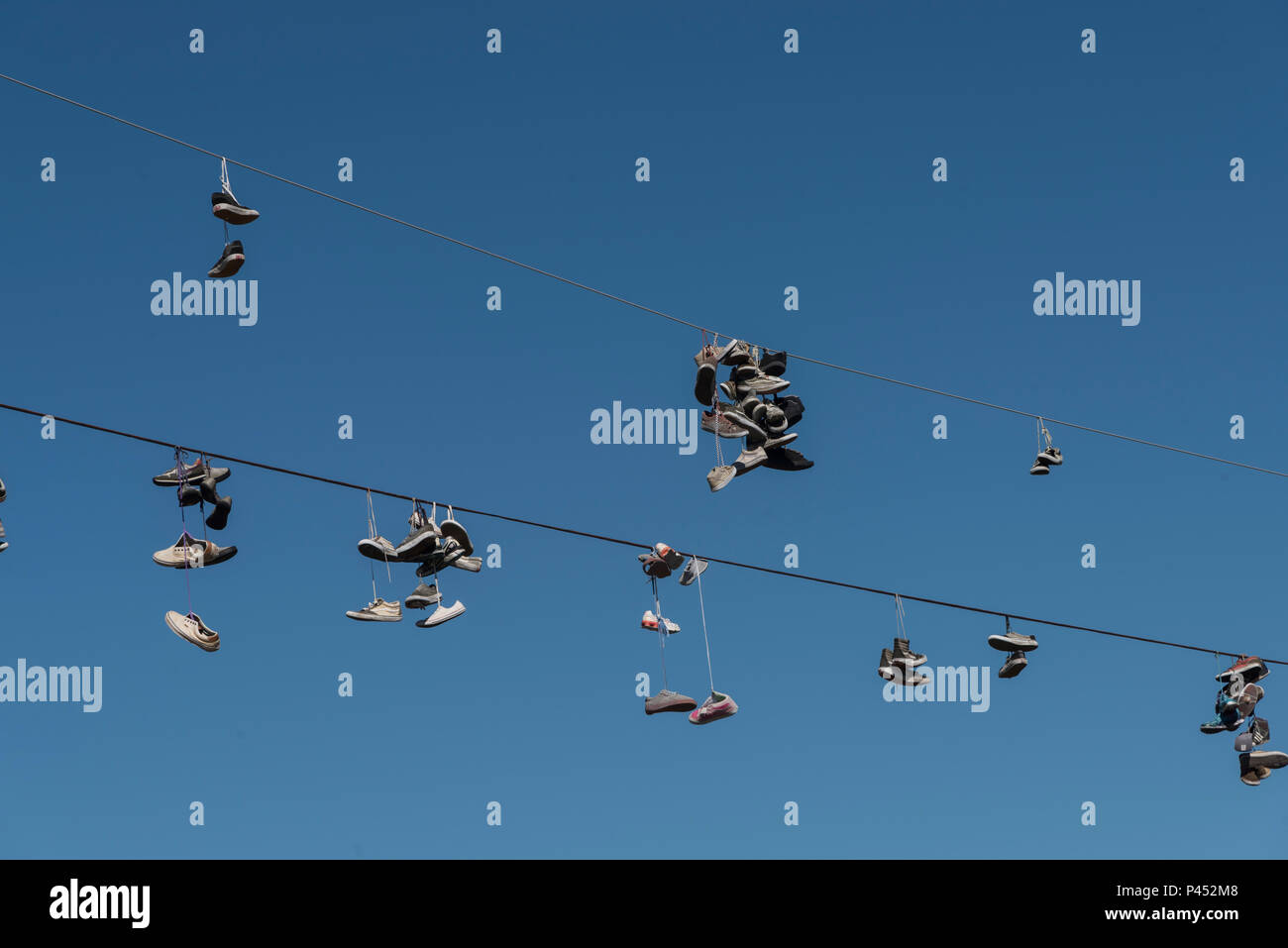 Low angle view of shoes hanging on overhead wires, Tofino, Vancouver Island, British Columbia, Canada - Stock Image