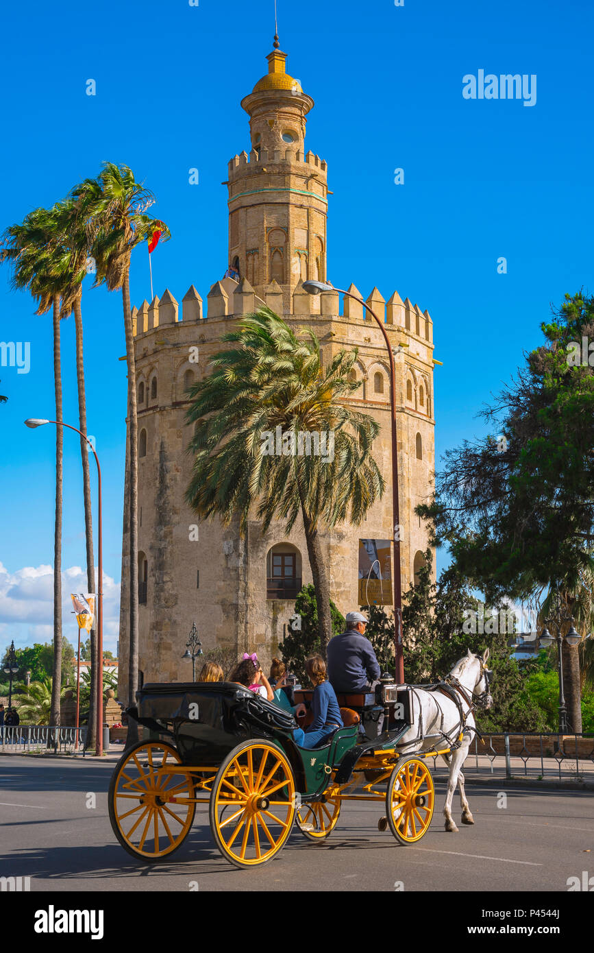 Seville Spain, tourists in a horse-drawn carriage ride past the Torre del Oro (Tower of Gold) in the old town quarter of Seville, Andalucia, Spain. - Stock Image