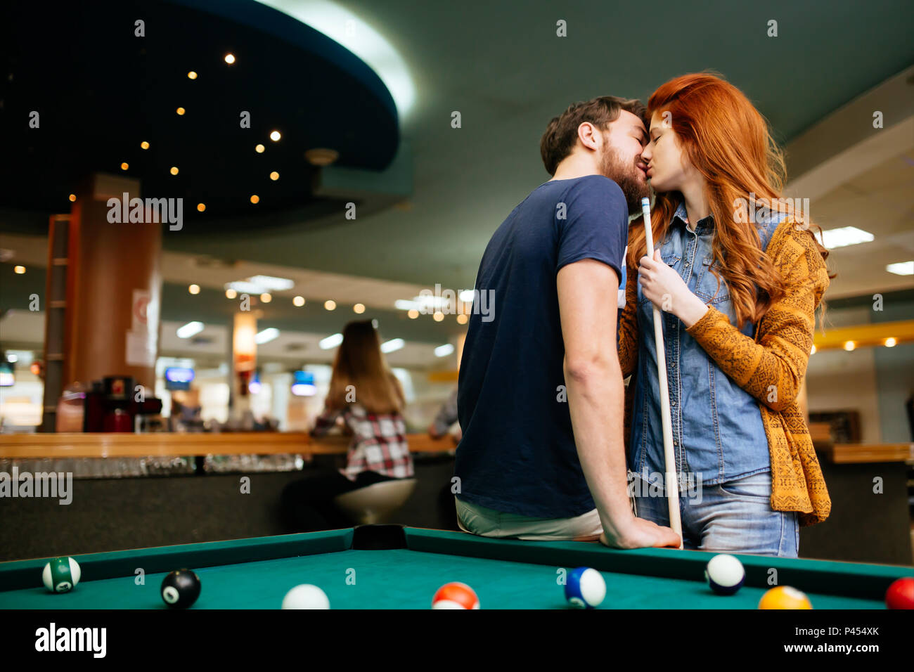 Beautiful couple kissing in billiards bar - Stock Image
