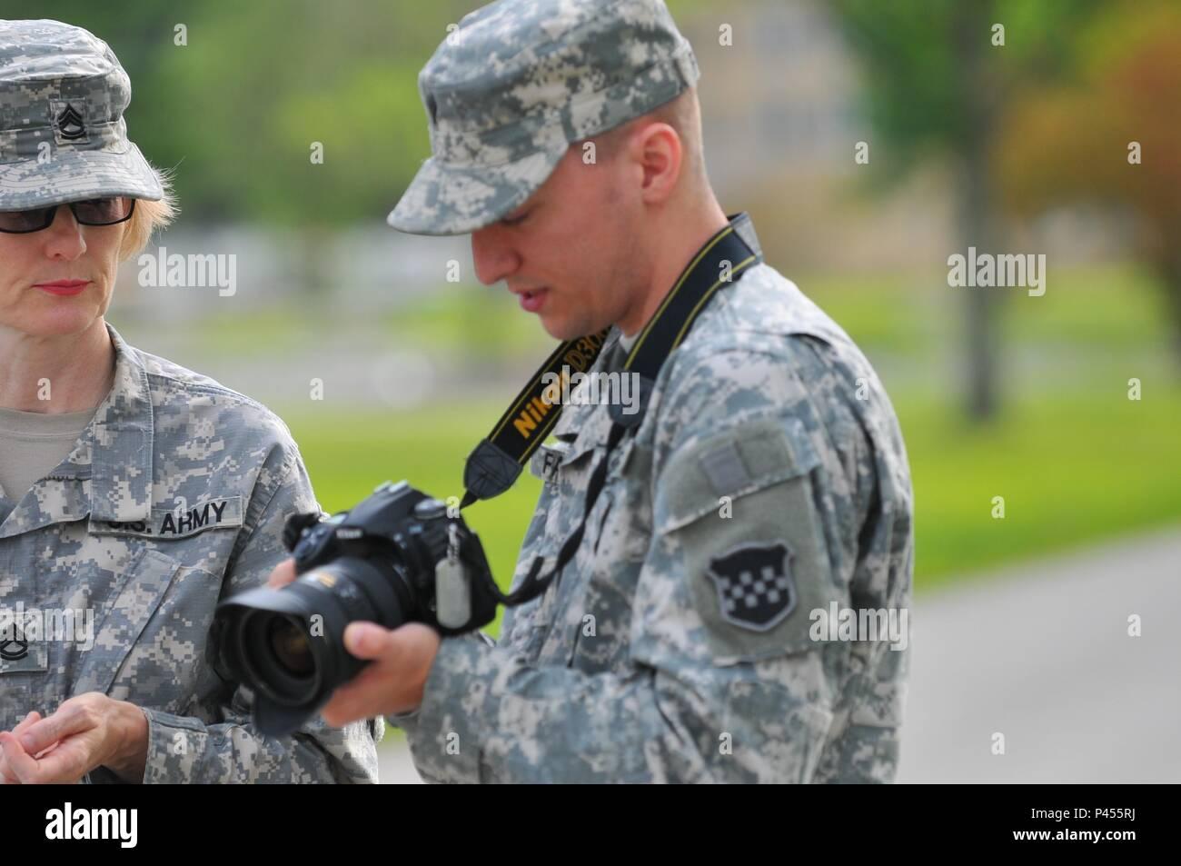 Sgt. 1st Class Elizabeth Breckenkamp (on left) trains Spec. Joe Falsetta on the Nikon D300 camera at Muscatatuck Urban Training Center, Ind., on June 14, 2016. - Stock Image
