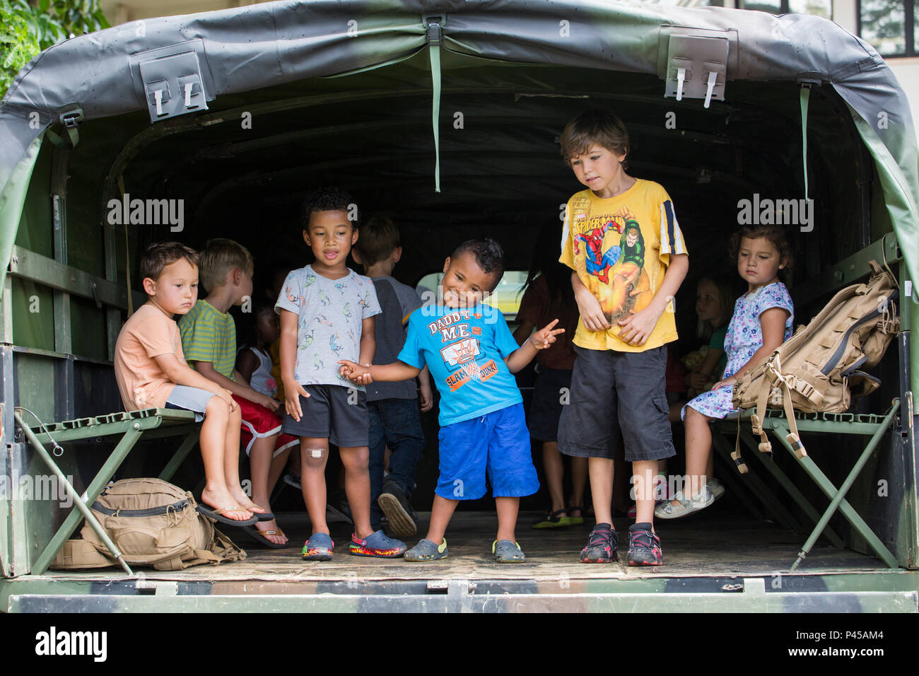 """KANEOHE, Hawaii – Children from the local community play in the back of a Medium Tactical Vehicle Replacement during a """"Meet the Community Heroes"""" event at the Kaneohe Public Library in Kaneohe, Hawaii, June 23, 2016. Children got to meet police officers, firefighters and Marines. Marines were given the opportunity to interact with children and parents as heroes from the community. Multiple vehicles from the organizations were on display for all the children to see and play in. (U.S. Marine Corps Photo by Lance Cpl. Jesus Sepulveda Torres) - Stock Image"""